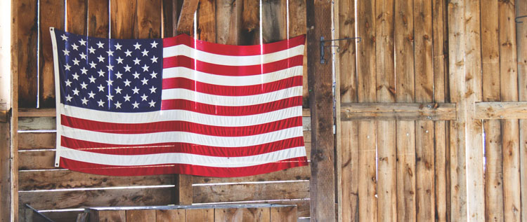 The American flag hangs on a barn wall