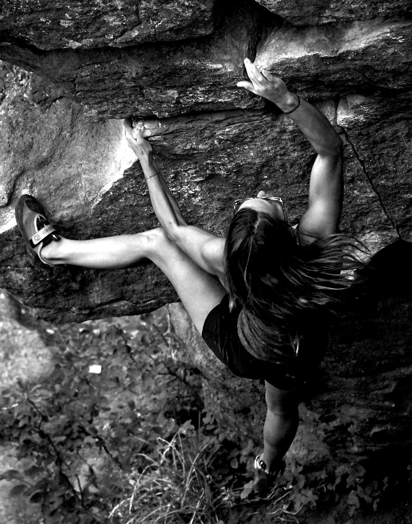 A woman climbs a rock face